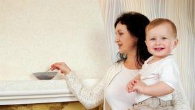 Мама подавая ее сын с вкусным пюрем с ложкой около камина, ребенка есть кашу с наслаждением акции видеоматериалы