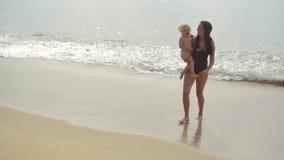 Мама при двухлетняя дочь идя вдоль песчаного пляжа видеоматериал