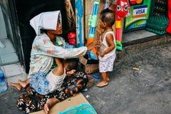 Мама при 2 дет ослабляя на тротуаре в Янгоне Стоковые Изображения RF