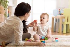Мама при младенец играя дома стоковая фотография