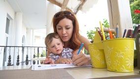 Мама при младенец сына покрашенный с покрашенными карандашами сток-видео