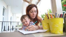 Мама при младенец сына покрашенный с покрашенными карандашами видеоматериал