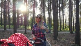Мама при прогулочная коляска показывая большие пальцы руки вверх сток-видео