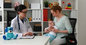 Мама при ребенок обсуждая с молодым доктором видеоматериал