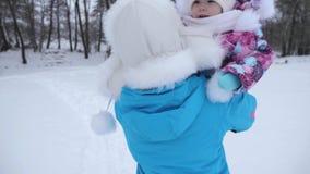 Мама продолжает младенца рук маленького идя вдоль снежной дороги в зиме Смех дочери в руках матери Прогулки родителя сток-видео