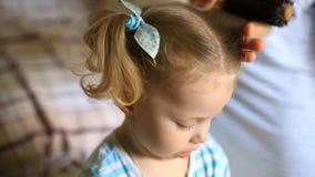 Мама расчесывает волосы к маленькой девочке с голубыми глазами видеоматериал