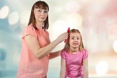 Мама расчесывает ее маленькие волосы ` s дочери стоковые изображения