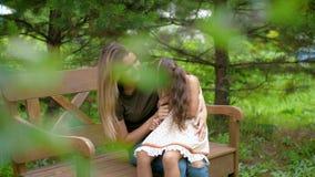 Мама сидит на стенде, она имеет маленькую девочку на ее подоле Женщина с детской игрой, беспечальным смехом, имеет потеху сидя на сток-видео