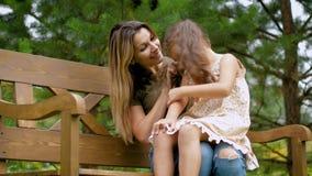 Мама сидит на стенде, она имеет маленькую девочку на ее подоле Женщина заплетает волосы к девушке, сидя на магазине среди зеленог видеоматериал