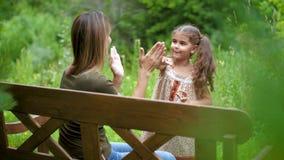 Мама сидит на стенде среди деревьев, она играет Пэт--торт с ребенком Женщина с детской игрой, беспечальным смехом видеоматериал