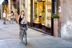 Мама с велосипедом катания дочери в Италии Ребенок сидя в безопасности Стоковые Изображения