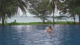 Мама с двухлетней дочерью в бассейне гостиницы около океана сток-видео