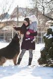 Мама с дочерью и собака на зиме идут Стоковые Фотографии RF