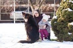 Мама с дочерью и собака на зиме идут Стоковые Изображения RF