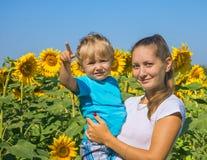 Мама с малым сыном среди солнцецветов Стоковое фото RF