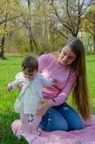 Мама с младенцем в ярких одеждах на розовой шотландке на зеленом праве Семья отдыхая в парке на теплый день стоковые изображения