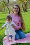 Мама с младенцем в ярких одеждах на розовой шотландке на зеленом праве Семья отдыхая в парке на теплый день стоковое фото