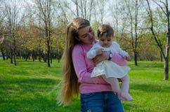 Мама с младенцем в ярких одеждах на розовой шотландке на зеленом праве Семья отдыхая в парке на теплый день стоковое изображение