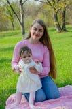 Мама с младенцем в ярких одеждах на розовой шотландке на зеленом праве Семья отдыхая в парке на теплый день стоковое изображение rf
