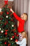 Мама с дочерью украшает дерево стоковая фотография