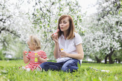 Мама с пузырями мыла красивой дочери дуя Стоковые Фотографии RF