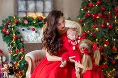 Мама с Рождеством Христовым и счастливых праздников жизнерадостная и ее милая девушка дочери обменивая подарки Родитель и меньший стоковое изображение rf