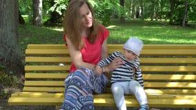 Мама с руками волны сына смотря камеру и обнять с любовью сток-видео