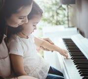 Мама уча ее играть рояля дочери Стоковое Изображение