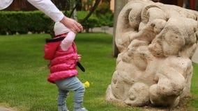 Мама учит милый ребёнок для того чтобы пойти к город-парку на зеленой траве сток-видео