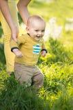 Мама учит траве сына идя стоковое изображение rf