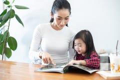 Мама учит, что ее дочь читает книгу стоковое изображение