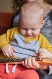 Мама учит, что ее маленький сын играет гитару Предыдущее развитие ребенка стоковое изображение rf