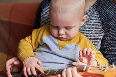Мама учит, что ее маленький сын играет гитару Предыдущее развитие ребенка стоковое фото rf