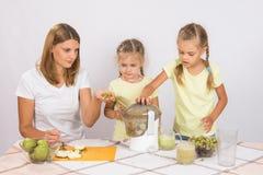 Мама учит, что дети сжимают сок в juicer Стоковые Изображения RF