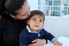 Мама целуя ее сына в ресторане Стоковые Фотографии RF