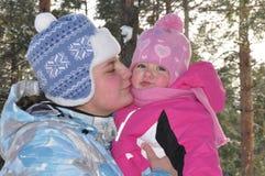 Мама целуя дочь младенца в снежном лесе. Стоковые Изображения