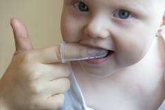 Мама чистит зубы щеткой младенца с щеткой которая приспосабливает на ее палец стоковое фото rf