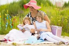 Мама читая книгу к его дочерям Стоковые Изображения RF