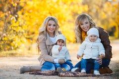 Мамы и дети для прогулки в парке в осени Стоковые Изображения
