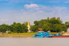 МАНДАЛАЙ, МЬЯНМА - 1-ОЕ ДЕКАБРЯ 2016: Голубая шлюпка около банка реки Irrawaddy, Бирмы Скопируйте космос для текста Стоковые Изображения