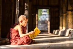 МАНДАЛАЙ, МЬЯНМА 18-ОЕ ФЕВРАЛЯ: Молодые монахи сидя и читая Стоковая Фотография