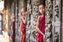 МАНДАЛАЙ, МЬЯНМА 18-ОЕ ФЕВРАЛЯ: Молодые монахи стоя и смотря Стоковые Фото