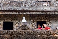 МАНДАЛАЙ, МЬЯНМА 18-ОЕ ФЕВРАЛЯ: Молодые монахи стоя и смотря Стоковые Изображения