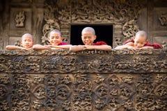 МАНДАЛАЙ, МЬЯНМА 18-ОЕ ФЕВРАЛЯ: Молодые монахи стоя и смотря Стоковые Фотографии RF