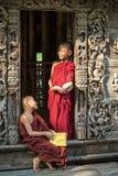 МАНДАЛАЙ, МЬЯНМА - 18-ОЕ ФЕВРАЛЯ: Молодые стоять и взгляд монахов послушника Стоковые Изображения RF