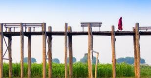 МАНДАЛАЙ - 19-ОЕ ФЕВРАЛЯ: Неопознанная прогулка на мосте U-Bein, февраль монаха Стоковая Фотография RF