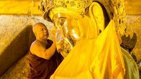 МАНДАЛАЙ - 19-ОЕ ФЕВРАЛЯ: Старшее изображение Mahamuni Будды мытья монаха внутри Стоковое Фото