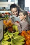 Мандарины матери и белокурой дочери покупая в магазине Стоковая Фотография