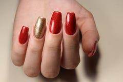 Маникюр пригвождает красный цвет и золото Стоковая Фотография RF