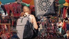 Манила, Филиппины - 26-ое ноября 2018: Кавказский женский путешественник с рюкзаком идя на азиатский уличный рынок внутри видеоматериал